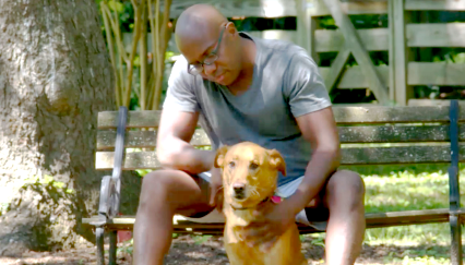 Raven who has tardive dyskinesia is sitting on a bench petting his dog